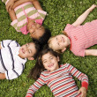 Children Lying in Clover With Heads Together — Zdjęcie stockowe #9228354