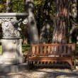 Bench and capital in park — Stock Photo