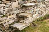 Stone steps into stonewall — Stockfoto