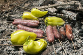Sausages and peppers on grill — Stock Photo