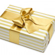 Gift box in gold duo tone with golden satin ribbon and bow isolated over white background. — Stock Photo #23681203