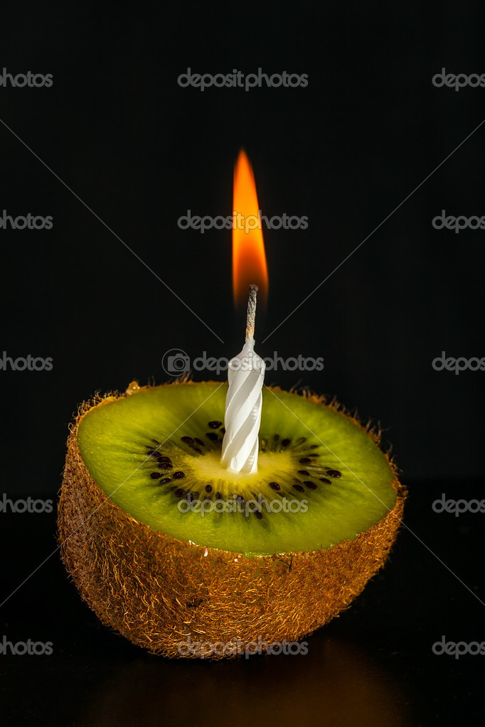 Romantic kiwi-shaped candle isolated on black background  Stock Photo #13928362