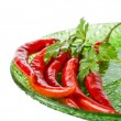 Red chili peppers on green plate — Stock Photo