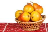Peras amarillas en cesta de mimbre en mantel rojo — Foto de Stock