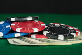 Chips and money on poker table — Stock Photo