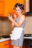 Casalinga di mezza età femmina dipinge le labbra in cucina — Foto Stock