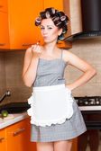 Female middle-aged housewife paints her lips in the kitchen — Stock Photo