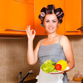 Beautiful woman in the kitchen with vegetables plate — Stock Photo