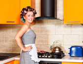 Middle-age woman with apron in the kitchen — Stock Photo