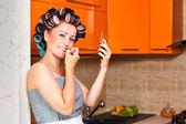 女性の中年の主婦、台所で彼女の唇を塗料します。 — ストック写真
