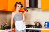 Middle-aged woman housewife in the kitchen with apple — Stock Photo