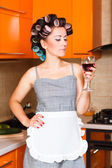 Female middle-aged housewife in the kitchen with glass of wine — Stock Photo