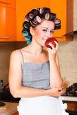 Kobieta w średnim wieku gospodyni w kuchni z jabłkiem — Zdjęcie stockowe