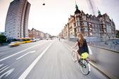Pretty girl riding bike, old buildings around. Denmark — Stock Photo