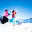 Two girls having great deal of fun jumping and riding boards — Stock Photo #28718401