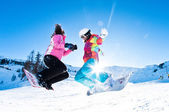 Two girls having great deal of fun jumping and riding boards — Stock Photo