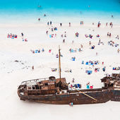 Castaways enjoying sunbathing on white sand beach near shipwreck — Stock Photo