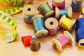 Reels of thread tapeline and two thimbles on wooden table — Stock Photo