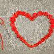 Heart in shape of red buttons and darning needle — Stock Photo #18971085