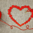 Heart in shape of red buttons, needle and yarn — Stock Photo