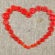 Heart of red buttons pierced needle — Stock Photo #18971093