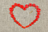 Heart of red buttons pierced needle — Stock Photo