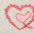 Heart in shape of red buttons and darning needle — Stock Photo