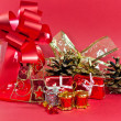 Christmas present in red and gold with ornaments — Stock Photo