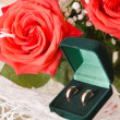 Stock Photo: Wedding rings and roses bouquet
