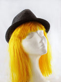 Model of polystyrene yellow wig grey hat — Stock Photo