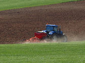 Tractor in the green field closeup — Stock Photo
