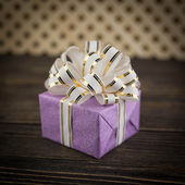 Gift box on old wooden background — Stock Photo