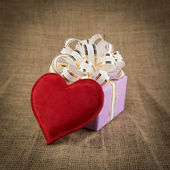 Gift box and heart on old background — Stock Photo