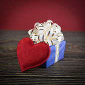 Gift box and heart on old wooden background — Stock Photo