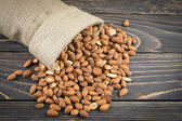 Almonds on rustic wooden background — Stock Photo