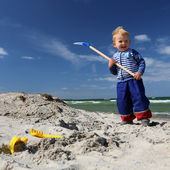 Boy with a shovel at the beach — Stock Photo