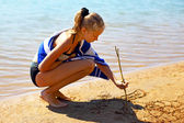 The girl draws on sea sand — Stock Photo