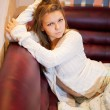 Stock Photo: Portrait of beautiful young woman on sofa