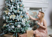Young beautiful woman in pink dress and christmass tree — Stockfoto