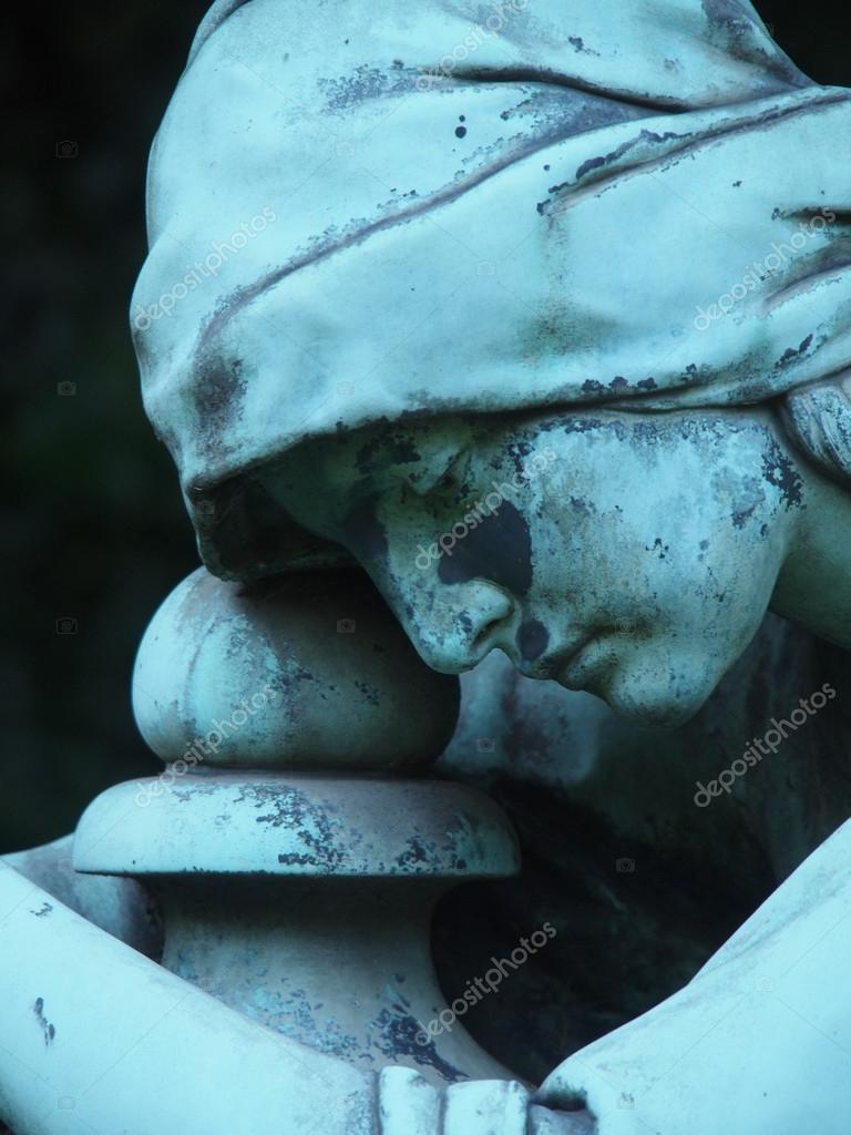 Detail of a gravestone statue showing the face of a sorrow woman — Photo #13343520