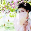 Geisha with fan in the garden — Stock Photo #15870641