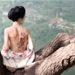 Woman with snake tattoo on her back on the tree branch (original) — Stock Photo #15870713