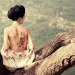 Woman with snake tattoo on her back on the tree branch — Stock Photo #15870717