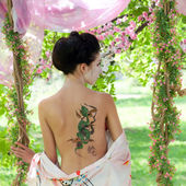 Woman with snake tattoo on her back in the garden — Stock Photo