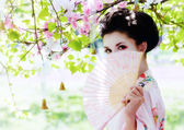 Geisha with fan in the garden — Stock Photo