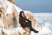 Buz kaplı kayada oturan esmer kız — Stok fotoğraf