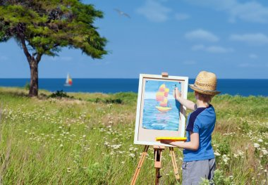 Young artist finishing his work, outdoor