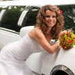 Stock Photo: Bride with original bouquet leaning on white car