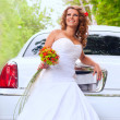 Bride with original bouquet near the white car — Stock Photo