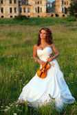 Smiling bride with violin in front of the ruins — Stock Photo